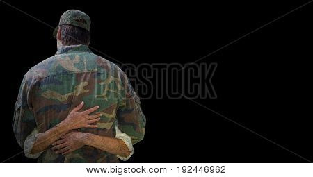 Digital composite of Back of soldier being hugged against black background with grunge overlay