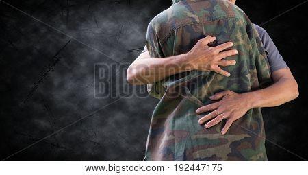 Digital composite of Soldier hugging mid section against black grunge background