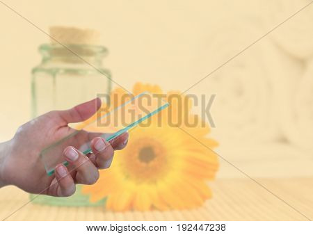 Digital composite of Hand holding glass screen next to sunflower and jar