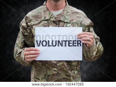 Digital composite of Soldier volunteer mid section against black grunge background