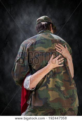 Digital composite of Back of soldier being hugged against black grunge background