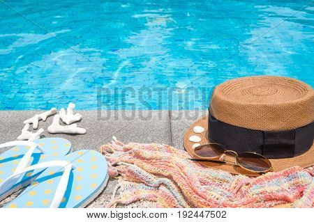 Concept of holiday tropical on summer Accessories blue slippers rainbow scarf straw hat shell coral and sunglasses on border of a swimming pool.