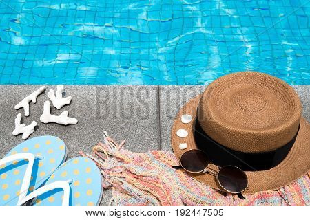 Concept of holiday tropical on summer Accessories blue slippers rainbow scarf straw hat shell coral and sunglasses on border of a swimming pool. View from above