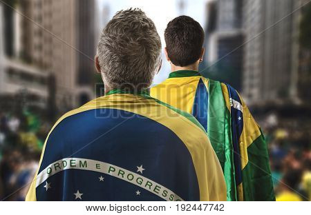 Brazilian couple holding the flag of Brazil in Paulista Avenue
