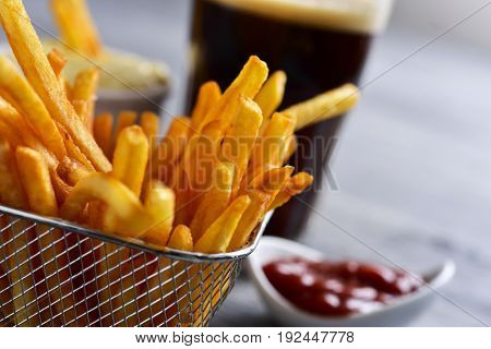 closeup of some appetizing french fries served in a metal basket, a glass with soda and some bowls with ketchup and mayonnaise, on a gray rustic wooden table