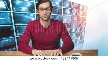 Digital composite of Hacker sitting at desk against monitors in background
