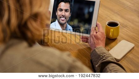 Digital composite of Rear view of man video conferencing with man at table
