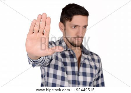 Young man doing stop gesture with hand. Isolated white background.