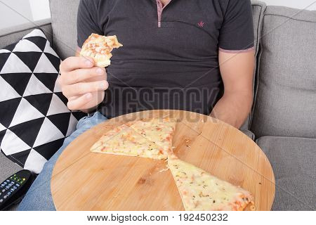 Man Eating Pizza On Couch.