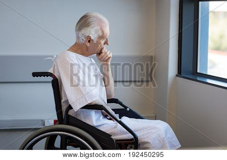Thoughtful senior man sitting on wheelchair at hospital. Sad disabled on wheelchair at the medical center feeling lonely. Retired man alone in a medical clinic.