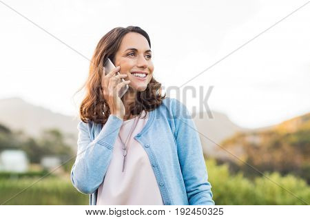 Mature happy woman talking on phone outdoor during sunset. Cheerful hispnic woman using smartphone and looking away. Happy woman in conversation using mobile phone and smiling.