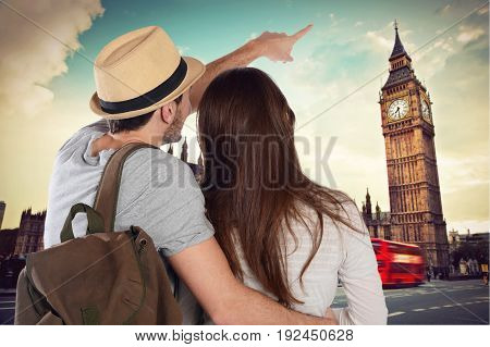 Back view of a traveling young couple and looking up to the Big Ben. Travel concept.