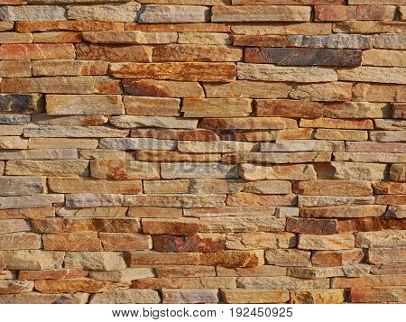 Brick stone bumpy fence background in warm sunset light