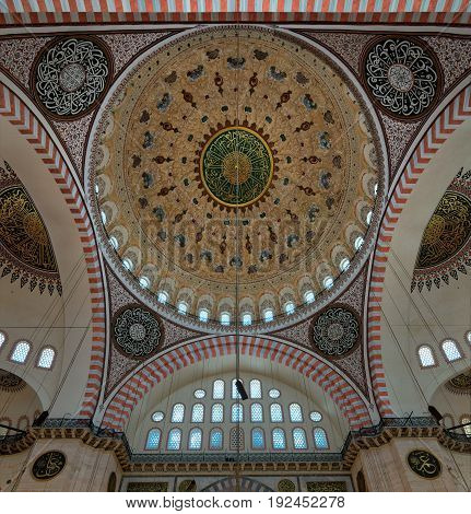 Istanbul, Turkey - April 19, 2017: Decorated ceiling of Suleymaniye Mosque with main dome and intersection of three arches