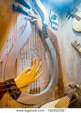 Shanghai, China - Nov 4, 2016: Night scene along Nanjing Road Pedestrian Street - Image shot through glass showing symbolic display of a Chinese lute or pipa, against lots of Chinese pictograms. Some reflections. Low-light street photography.