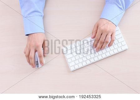 Male hands with computer mouse and keyboard on wooden background