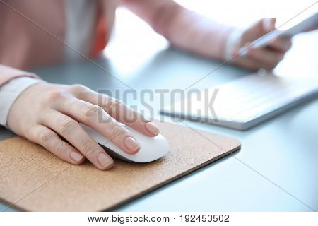 Female hand holding computer mouse on pad