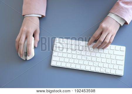 Female hands with computer mouse and keyboard on grey table