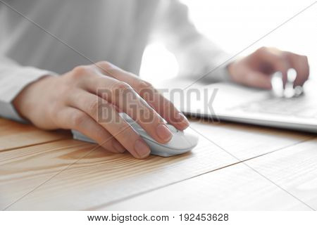 Female hand holding computer mouse on wooden table