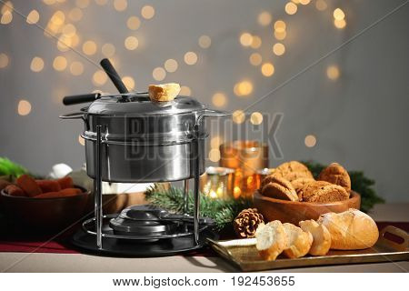 Fondue pot and fresh bread on table