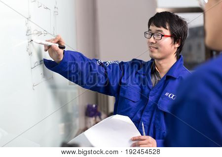jinhua,china-Jan 23,2017:two technician discuss technique in manufacturing factory