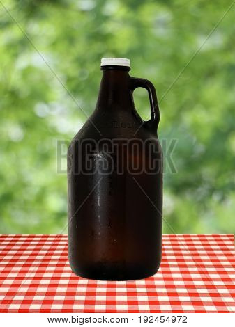 Growler at on Red Checkered Tablecloth against Blurry Trees
