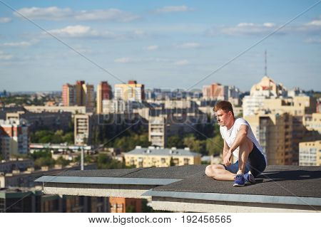 Roofer on the edge of the roof. A man is looking away from a high-rise building. Courage and adrenaline. Roofing