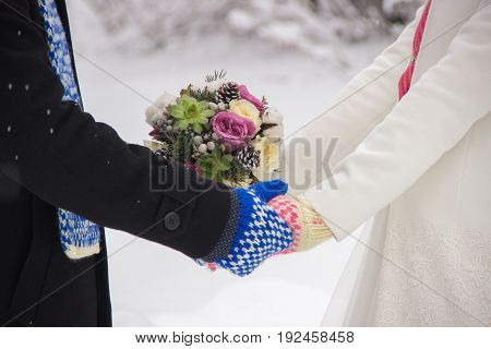 Wedding of a young girl and a guy in winter. Mittens blue and pink color.