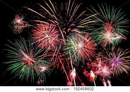 Fireworks lit up beautifully and filled the dark black sky with gold red pink green white light at night time to celebrate new year eve festival fourth of July and special occasion