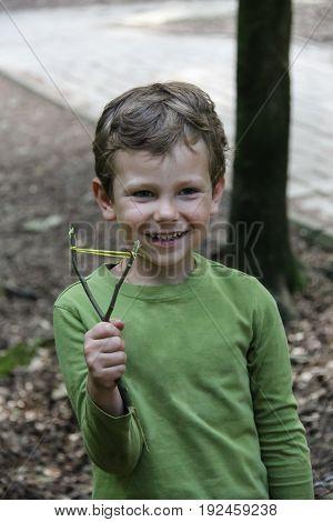 Smiling boy with makeshift slingshot in summer forest park