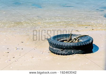 Abandoned rusty tyre full of waste on dirty beach.