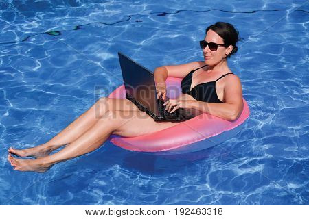 Middle aged female executive workaholic working on laptop computer in pink inflatable life ring in swimming pool on vacation