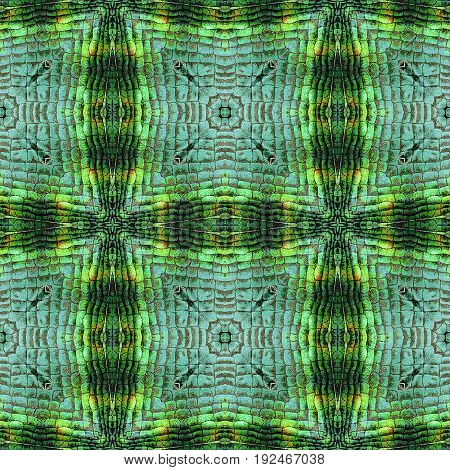 Abstract seamless pattern of squares and scales resembling snake skin. Green black orange and yellow kaleidoscopic background with reptile scales