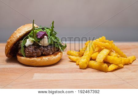 Picture of a tasty gorgonzola cheeseburger with rucola and french fries