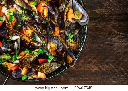 A closeup of a skillet of marinara mussels, shot from above on a dark rustic background texture with a place for text