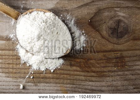 Organic wheat flour in wooden spoon on wooden rustic background with copy space