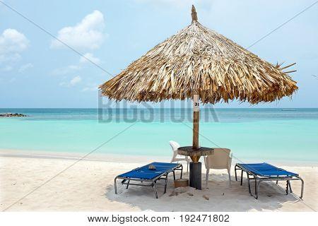 Beach umbrella and beach chairs on Palm Beach at Aruba island in the Caribbean Sea