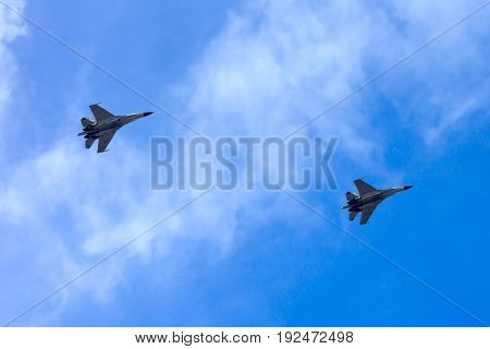 A couple of combat aircrafts flyby in an airshow with blue sky on the background. They are consist of single seat and double seats fighter jets.
