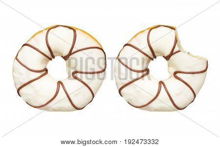 Two delicious white chocolate donuts glazed with dark chocolate flower shapes isolated on white background. One sweet donut with icing sugar was bitten.
