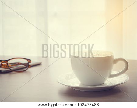 coffee cup of cappuccino with eyeglasses on smartphone tablet cell phone with blurry white drape texture background warm tone view from front wood table.