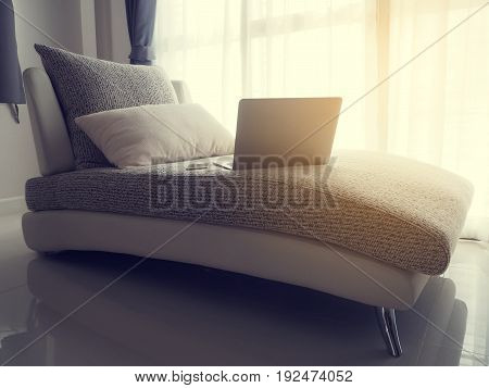 laptop on modern sofa at living room with warm sunlight in the morning warm tone.