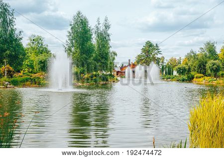 Summer city Park with fountains in the lake. Mezhyhirya