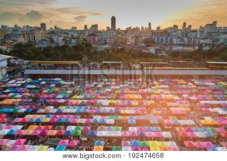 City night market aerial view multiple colour flea market and downtown background