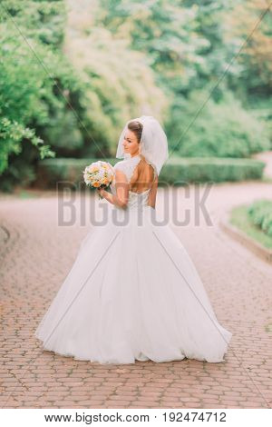 The full-length back view of the bride with bare shoulder holding the wedding bouquet at the background of the park