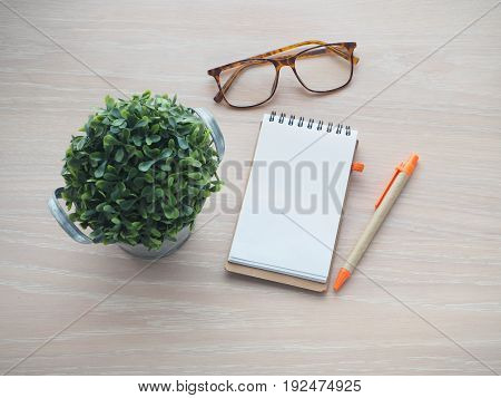 wood office table with small tree on pot modern eyeglasses and blank screen on notepad paper. view from top office table.