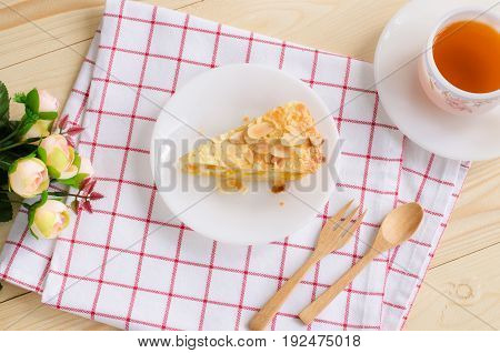 Flat lay image of a piece of delicious corn pie on white ceramic plate over red & white scott pattern cloth with black tea in white cup & saucer wooden fork & spoon and small roses over wooden table