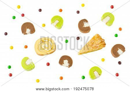 Flat lay image of Swiss roll corn pie chocolate and pandan cake rolls with sweet multi-color candies isolated on white background for happy party time celebration or fun and special occasion