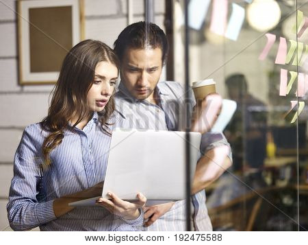 asian businessman and caucasian businesswoman working together using laptop computer in office.