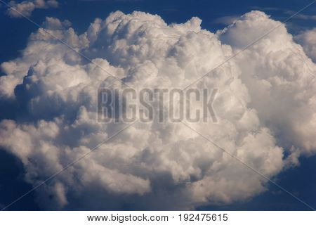 Aerial view from the airplane window to a fluffy cloud. Sky backround