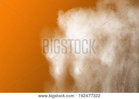 Abstract white powder explosion on orange background.